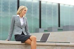 Eine junge blonde Geschäftsfrau, die draußen arbeitet Stockbilder