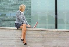 Eine junge blonde Geschäftsfrau, die draußen arbeitet Stockfotos