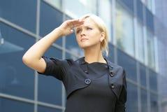 Eine junge blonde Geschäftsfrau, die irgendwo schaut Stockbilder