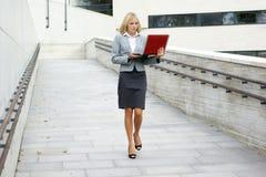 Eine junge blonde Geschäftsfrau, die mit einem Laptop geht Stockfotografie