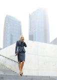 Eine junge blonde Geschäftsfrau, die am Telefon spricht Stockfotografie