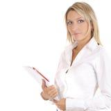 Eine junge blonde Geschäftsfrau mit einem Faltblatt Lizenzfreies Stockfoto