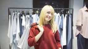 Eine junge blonde glückliche lächelnde Frau kaufte gerade Kleidung in einem Shop Stockbild