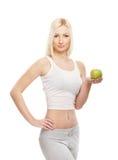 Eine junge blonde kaukasische Frau, die einen Apfel anhält Lizenzfreie Stockbilder