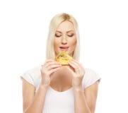 Eine junge blonde kaukasische Frau, die einen Hamburger isst Stockbilder
