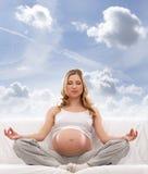 Eine junge blonde kaukasische schwangere meditierende Frau Stockfotos