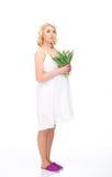 Eine junge blonde schwangere Frau, die Blumen hält Stockfotografie