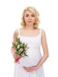 Eine junge blonde schwangere Frau, die Blumen hält Stockbilder