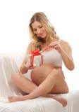 Eine junge blonde schwangere Frau, die ein Geschenk öffnet Stockfotos
