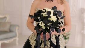 Eine junge Blondine in einem schwarzen Kleid mit einem Blumenstrauß von schwarzen Blumen Halloween stock video