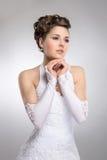 Eine junge Brunettebraut, die in einem weißen Kleid aufwirft Stockfotos