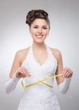 Eine junge Brunettebraut, die in einem weißen Kleid mit einem Band aufwirft Lizenzfreie Stockbilder