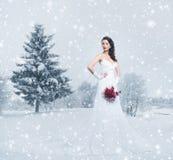 Eine junge Brunettebraut in einem weißen Kleid auf dem Schnee Lizenzfreie Stockbilder