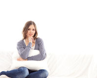 Eine junge Brunettefrau, die auf einem weißen Sofa sich entspannt Lizenzfreies Stockbild