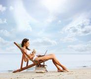 Eine junge Brunettefrau, die ein Cocktail trinkt und auf dem Strand sich entspannt Stockfotos