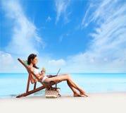 Eine junge Brunettefrau, die ein Cocktail trinkt und auf dem Strand sich entspannt Lizenzfreies Stockbild