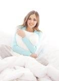 Eine junge Brunettefrau, die in einem weißen Bett sich entspannt Lizenzfreie Stockfotografie