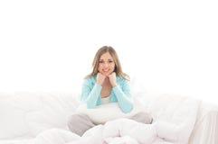 Eine junge Brunettefrau, die in einem weißen Bett sich entspannt stockfotografie