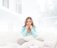 Eine junge Brunettefrau, die in einem weißen Bett sich entspannt Lizenzfreies Stockfoto