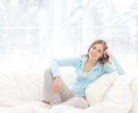 Eine junge Brunettefrau, die in einem weißen Bett sich entspannt Lizenzfreie Stockfotos