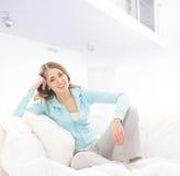 Eine junge Brunettefrau, die in einem weißen Bett sich entspannt Lizenzfreies Stockbild