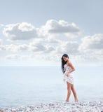 Eine junge Brunettefrau, die nahe dem Meer geht Stockbilder