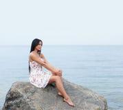 Eine junge Brunettefrau, die nahe dem Meer sitzt Stockbilder