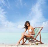 Eine junge Brunettefrau, die Suntan auf dem Strand hinzufügt Stockfoto