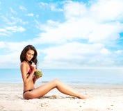 Eine junge Brunettefrau in einem Badeanzug ein Cocktail trinkend Lizenzfreies Stockfoto