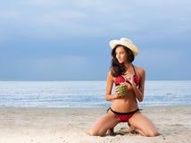 Eine junge Brunettefrau in einem Badeanzug ein Cocktail trinkend Lizenzfreie Stockbilder