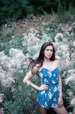 Eine junge Brunettefrau im blauen Overall, der im hohen Gras steht Stockfoto