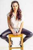 Eine junge Brunettefrau im weißen Hemd, das aggressiv auf einem Stuhl aufwirft Stockbild