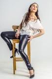 Eine junge Brunettefrau im weißen Hemd, das aggressiv auf einem Stuhl aufwirft Lizenzfreie Stockbilder