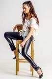 Eine junge Brunettefrau im weißen Hemd, das aggressiv auf einem Stuhl aufwirft Lizenzfreie Stockfotografie
