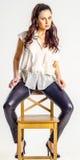 Eine junge Brunettefrau im weißen Hemd, das aggressiv auf einem Stuhl aufwirft Stockfoto