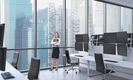 Eine junge Dame in der Abendtoilette hält einen schwarzen Dokumentenordner im modernen panoramischen Büro in Singapur Weiße Tabel Lizenzfreie Stockbilder
