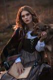 Eine junge Dame in einem mittelalterlichen Kleid mit einem Hund und einem Buch Stockbilder