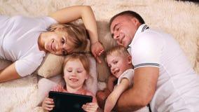 Eine junge Familie auf ihren Lügen und Resten des freien Tages auf dem Bett, lächelnd und betrachten die Tablette mit den Kindern stock footage