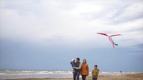 Eine junge Familie geht entlang den Strand im kühlen Wetter mit einem Drachen stock footage