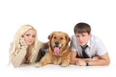 Eine junge Familie mit einem Hund auf Fußboden Stockfotografie