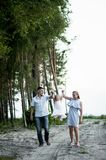 Eine junge Familie mit einer kleinen Tochter, die entlang einen sandigen Weg geht Lizenzfreie Stockfotos