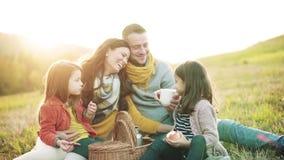 Eine junge Familie mit zwei kleinen Kindern, die Picknick in der Herbstnatur haben stock video footage