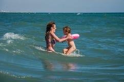 Eine junge Familie, eine Mutter und eine Tochter mit einer Schwimmen kreisen ein und spielen auf dem Strand auf dem Strand der ty Stockfoto