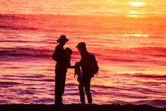 Eine junge Familie, welche die Ozeanformschattenbilder gegen die untergehende Sonne genießt Stockfotografie