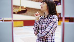 Eine junge Frau überprüft die Ausstellung in der Galerie stock video footage