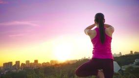 Eine junge Frau übt Yoga auf einem Berg im Hintergrund von einer Großstadt Gesunde Frau, die Sport bei Sonnenuntergang tut A stock video footage