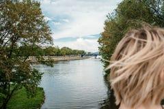 Eine junge Frau auf der Weichsel in Krakau Stilvolles Mädchen in der Sonnenbrille spricht an ihrem Telefon Ansicht der Stadt von  stockfotografie