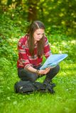 Eine junge Frau betrachtet eine Karte beim Wandern Stockfoto