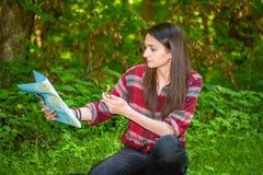 Eine junge Frau betrachtet eine Karte beim Wandern Stockbilder