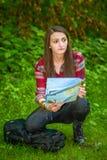 Eine junge Frau betrachtet eine Karte beim Wandern Lizenzfreies Stockfoto